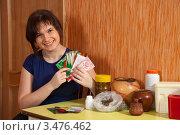 Купить «Женщина за столом на кухне держит пакеты с семенами», фото № 3476462, снято 31 января 2012 г. (c) Яков Филимонов / Фотобанк Лори