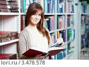 Купить «Улыбающаяся девушка с книгой в руке стоит в библиотеке на фоне стеллажей», фото № 3478578, снято 24 января 2012 г. (c) Дмитрий Калиновский / Фотобанк Лори