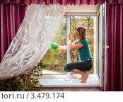 Купить «Женщина моет окно в квартире сидя на подоконнике», эксклюзивное фото № 3479174, снято 27 апреля 2012 г. (c) Игорь Низов / Фотобанк Лори