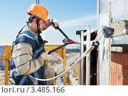 Купить «Монтажник крепит навесную фасадную систему на стену здания», фото № 3485166, снято 10 апреля 2012 г. (c) Дмитрий Калиновский / Фотобанк Лори