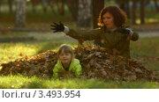 Мать и дочь в куче осенних листьев. Стоковое видео, видеограф Павел Меняйло / Фотобанк Лори