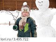Мальчик в зимней одежде стоит у снеговика. Стоковое фото, фотограф Хромушин Тарас / Фотобанк Лори