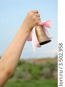 Купить «Рука держит бронзовый колокольчик с розовой лентой», фото № 3502958, снято 5 мая 2012 г. (c) Сергей Галушко / Фотобанк Лори