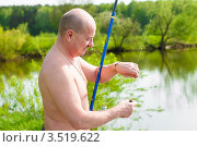 Купить «Мужчина снимает пойманную рыбу с крючка», эксклюзивное фото № 3519622, снято 15 мая 2012 г. (c) Игорь Низов / Фотобанк Лори
