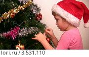 Купить «Девочка в колпаке Санты-Клауса вешает гирлянду на елку», видеоролик № 3531110, снято 28 декабря 2008 г. (c) Losevsky Pavel / Фотобанк Лори