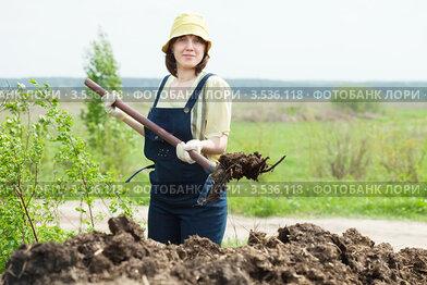Женщина удобряет огород навозом