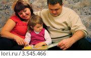 Купить «Мама, папа и дочка читают детскую книгу», видеоролик № 3545466, снято 10 ноября 2009 г. (c) Losevsky Pavel / Фотобанк Лори