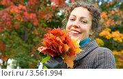 Купить «Улыбающаяся женщина с букетом осенних листьев в руках», видеоролик № 3561994, снято 24 декабря 2009 г. (c) Losevsky Pavel / Фотобанк Лори