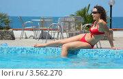Купить «Молодая женщина в красном купальнике отдыхает у бассейна», видеоролик № 3562270, снято 3 января 2010 г. (c) Losevsky Pavel / Фотобанк Лори
