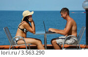 Купить «Мужчина и женщина сидят с ноутбуком и телефоном за столом на фоне моря», видеоролик № 3563290, снято 13 января 2010 г. (c) Losevsky Pavel / Фотобанк Лори