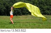 Купить «Женщина держит развевающееся желтое полотно над головой», видеоролик № 3563922, снято 3 февраля 2010 г. (c) Losevsky Pavel / Фотобанк Лори