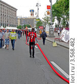 Купить «Подготовка в ЕВРО 2012 на Крещатике в г. Киев. Рабочие тянут красный кабель по асфальту», фото № 3568482, снято 2 июня 2012 г. (c) FMRU / Фотобанк Лори