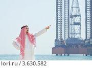 Купить «Араб показывает на нефтяную вышку в море», фото № 3630582, снято 12 мая 2012 г. (c) Elnur / Фотобанк Лори