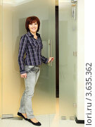 Купить «Одетая  в рубашку и джинсы счастливая женщина стоит возле прозрачной двери», фото № 3635362, снято 18 мая 2011 г. (c) Losevsky Pavel / Фотобанк Лори