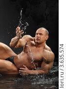 Купить «Мускулистый мужчина лежит в воде и играет с брызгами», фото № 3635574, снято 2 апреля 2011 г. (c) Losevsky Pavel / Фотобанк Лори