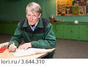 Пожилой мужчина пишет отчет в журнал на рабочем месте. Стоковое фото, фотограф Кекяляйнен Андрей / Фотобанк Лори