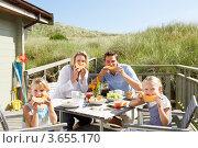 Купить «Семейство ест дыню за столом на природе», фото № 3655170, снято 27 августа 2010 г. (c) Monkey Business Images / Фотобанк Лори