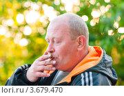 Купить «Мужчина на улице курит сигарету», эксклюзивное фото № 3679470, снято 3 июня 2012 г. (c) Игорь Низов / Фотобанк Лори