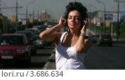 Купить «Брюнетка слушает музыку в наушниках на дороге», видеоролик № 3686634, снято 26 марта 2010 г. (c) Losevsky Pavel / Фотобанк Лори