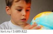 Мальчик смотрит на подсвеченный глобус и вращает его. Стоковое видео, видеограф Losevsky Pavel / Фотобанк Лори