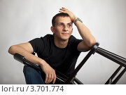 Купить «Улыбающийся молодой человек сидит со стулом в руках», фото № 3701774, снято 22 июля 2012 г. (c) Gagara / Фотобанк Лори