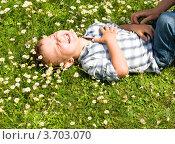Рука щекочет маленького мальчика, лежащего летом на траве на спине. Стоковое фото, фотограф Константин Примачук / Фотобанк Лори