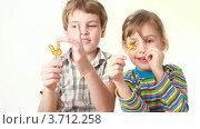 Мальчик и девочка облизывают леденцы. Стоковое видео, видеограф Losevsky Pavel / Фотобанк Лори