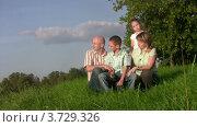 Купить «Семья сидит в траве и смотрит вдаль», видеоролик № 3729326, снято 6 апреля 2011 г. (c) Losevsky Pavel / Фотобанк Лори