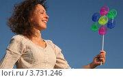 Купить «Женщина стоит на фоне неба  и держит в руках игрушку ветряную мельницу», видеоролик № 3731246, снято 22 марта 2011 г. (c) Losevsky Pavel / Фотобанк Лори