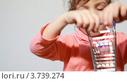 Купить «Маленькая красивая девочка играет с моделью маленькой торговой тележки», видеоролик № 3739274, снято 3 июня 2011 г. (c) Losevsky Pavel / Фотобанк Лори