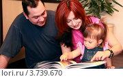 Купить «Родители и маленькая девочка сидят на полу, читая книгу», видеоролик № 3739670, снято 1 мая 2011 г. (c) Losevsky Pavel / Фотобанк Лори