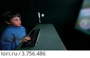 Купить «Мальчик жует резинку и играет d видео игры с клавиатуры на большом экране», видеоролик № 3756486, снято 25 декабря 2011 г. (c) Losevsky Pavel / Фотобанк Лори
