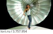 Купить «Девушка с длинными волосами и в джинсах танцует на фоне зонтика в фотостудии», видеоролик № 3757954, снято 30 ноября 2011 г. (c) Losevsky Pavel / Фотобанк Лори