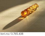 Янтарные шарики на пергаменте в луче света. Стоковое фото, фотограф Марина Алешина / Фотобанк Лори