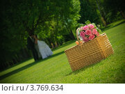 Свадебный букет лежит на плетеной корзине. На заднем плане стоят молодожены. Стоковое фото, фотограф Алексей Казнадей / Фотобанк Лори
