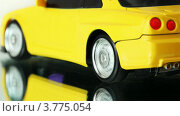 Купить «Желтая радиоуправляемая машинка на зеркальной поверхности», видеоролик № 3775054, снято 15 марта 2012 г. (c) Losevsky Pavel / Фотобанк Лори