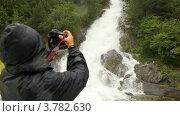 Купить «Человек в плаще фотографирует падающий поток», видеоролик № 3782630, снято 5 июня 2012 г. (c) Losevsky Pavel / Фотобанк Лори