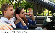 Купить «Молодой человек и девушка сидят на переднем сидении в кабриолете и смотрят в зеркало заднего вида летним днем», видеоролик № 3783014, снято 28 апреля 2012 г. (c) Losevsky Pavel / Фотобанк Лори
