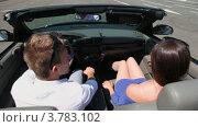 Купить «Молодой человек и девушка едут  в кабриолете по городу и улыбаются летним днем», видеоролик № 3783102, снято 26 апреля 2012 г. (c) Losevsky Pavel / Фотобанк Лори