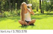 Девушка сидит на траве в парке и пьет воду летом. Стоковое видео, видеограф Максим Шатохин / Фотобанк Лори