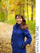 Купить «Веселая девушка в синем пальто стоит в осеннем парке», фото № 3797342, снято 27 сентября 2011 г. (c) Яков Филимонов / Фотобанк Лори