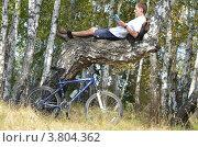 Молодой человек читает книгу на дереве (2012 год). Редакционное фото, фотограф Воробьев Валерий / Фотобанк Лори