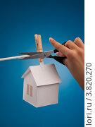 Рука с ножницами перерезает веревку с домиком. Стоковое фото, фотограф Vycheslav Leskovskiy / Фотобанк Лори