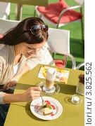 Девушка ест десерт в открытом кафе. Стоковое фото, фотограф CandyBox Images / Фотобанк Лори