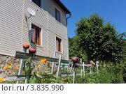 Купить «Ограда палисадника с горшками на фоне стены с окнами», фото № 3835990, снято 10 июня 2012 г. (c) Юлия Ухина / Фотобанк Лори