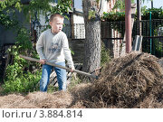 Мальчик ворошит сено (2012 год). Редакционное фото, фотограф Сергей Хрушков / Фотобанк Лори