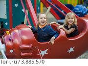 Купить «Две веселые сестры на карусели в городском парке», фото № 3885570, снято 4 июня 2012 г. (c) BestPhotoStudio / Фотобанк Лори