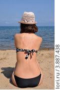 Стройная девушка в купальнике и шляпе сидит спиной на фоне озера Байкал. Стоковое фото, фотограф Kirill Kazakov / Фотобанк Лори