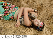 Красивая девушка хиппи лежит в сухой траве. Стоковое фото, фотограф Boris Bushmin / Фотобанк Лори