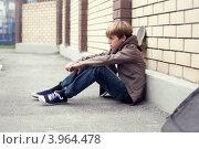 Расстроенный школьник задумался сидя на улице. Стоковое фото, фотограф Римма Зайцева / Фотобанк Лори